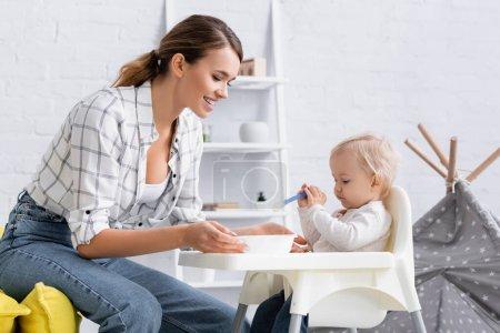 Photo pour Petit garçon assis sur une chaise enfant avec cuillère près de mère heureuse - image libre de droit