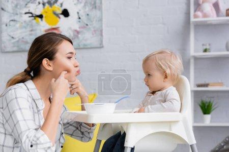 Photo pour Jeune femme toucher le visage tout en regardant bébé garçon assis sur chaise enfants près bol - image libre de droit