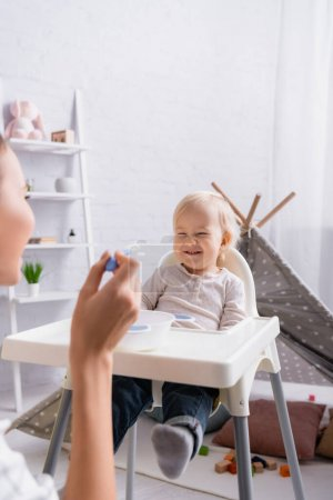 Photo for Woman holding spoon near cheerful baby boy sitting on kids chair, blurred foreground - Royalty Free Image