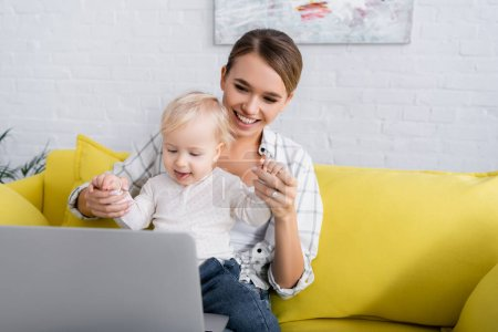 Photo for Happy freelancer holding hands of little son near laptop on yellow sofa - Royalty Free Image