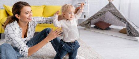 Foto de Alegre madre ayudar a niño pequeño de pie en el suelo en casa, pancarta - Imagen libre de derechos