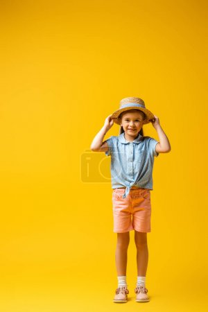 Photo for Full length of happy child adjusting straw hat on yellow - Royalty Free Image