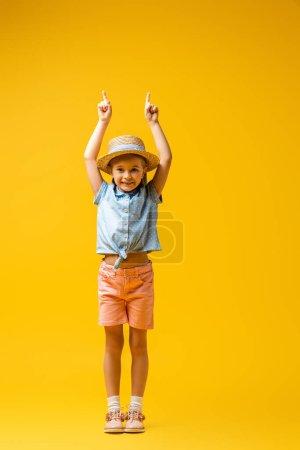 Photo pour Pleine longueur de l'enfant gai dans le chapeau de paille pointant vers le haut avec les doigts sur le jaune - image libre de droit