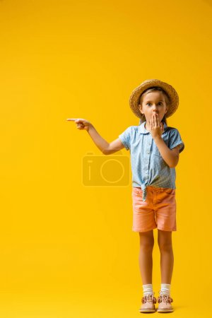 full length of shocked kid in straw hat covering mouth and pointing with finger on yellow