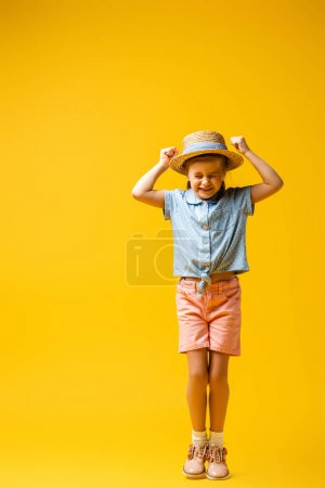 Photo pour Pleine longueur de gamin excité avec les poings serrés sur jaune - image libre de droit