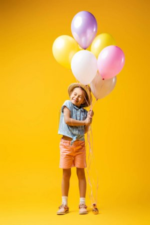 Photo pour Pleine longueur de gosse heureux en chapeau de paille tenant des ballons sur jaune - image libre de droit
