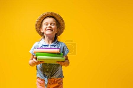 Photo pour Enfant joyeux en chapeau de paille tenant des livres isolés sur jaune - image libre de droit