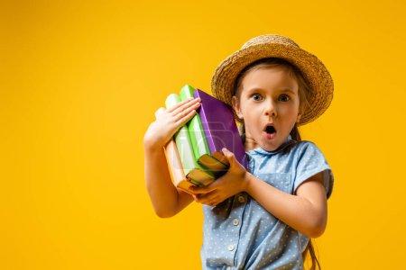 Photo pour Fille surprise en chapeau de paille tenant des livres isolés sur jaune - image libre de droit