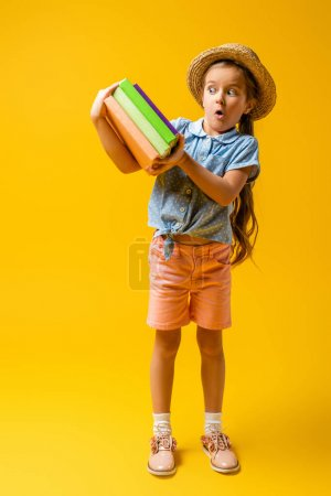Photo pour Pleine longueur de fille surprise en chapeau de paille regardant des livres sur le jaune - image libre de droit