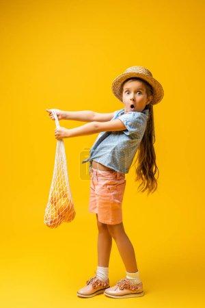 Photo pour Pleine longueur de fille choquée dans un chapeau de paille tenant sac à ficelle réutilisable avec des oranges sur jaune - image libre de droit
