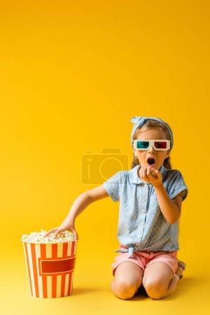 verblüfftes Kind in 3D-Gläsern isst Popcorn und greift nach Eimer auf gelb