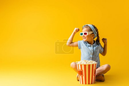 smiling kid in 3d glasses sitting with crossed legs near popcorn bucket on yellow