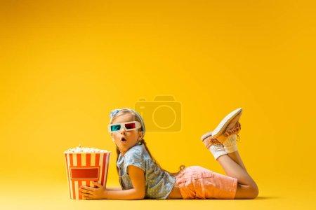 shocked girl in 3d glasses lying near popcorn bucket on yellow