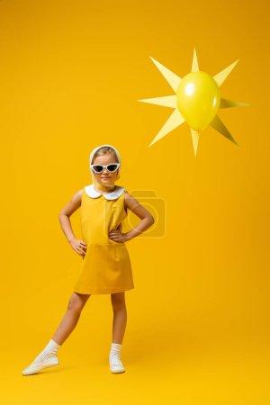 Photo pour Pleine longueur de fille en foulard et lunettes de soleil debout avec les mains sur les hanches près du soleil décoratif avec ballon sur jaune - image libre de droit