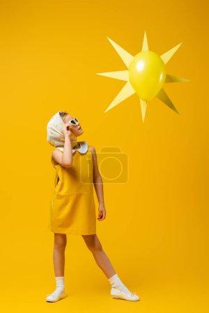 Photo pour Pleine longueur de fille en foulard et lunettes de soleil regardant le soleil décoratif avec ballon sur jaune - image libre de droit