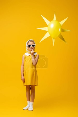 full length of pensive girl in headscarf and sunglasses standing near decorative sun with balloon on yellow