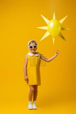 full length of happy girl in headscarf and sunglasses pointing with finger at decorative sun with balloon on yellow