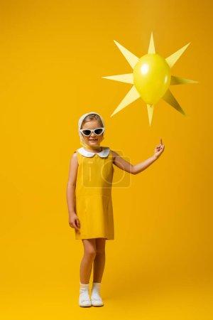 Photo pour Pleine longueur de fille heureuse dans le foulard et les lunettes de soleil pointant du doigt au soleil décoratif avec ballon sur jaune - image libre de droit