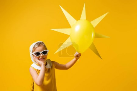 Photo for Happy girl in headscarf and sunglasses near decorative sun with balloon isolated on yellow - Royalty Free Image