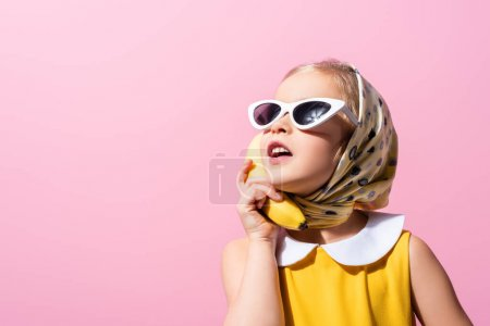 Photo for Girl in headscarf and sunglasses holding banana near ear isolated on pink - Royalty Free Image
