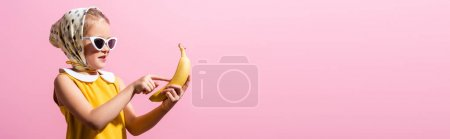 happy girl in headscarf and sunglasses pointing with finger at banana isolated on pink, banner