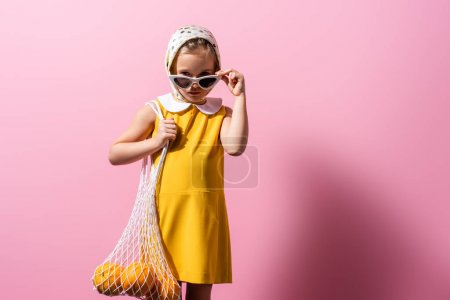 Photo for Girl in headscarf adjusting sunglasses while holding reusable string bag with oranges on pink - Royalty Free Image