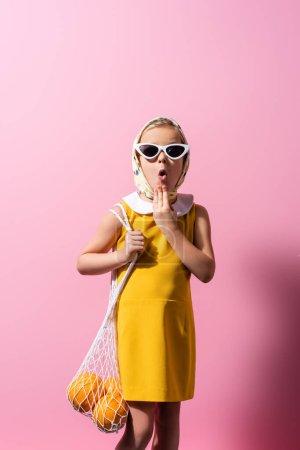 Schockiertes Mädchen mit Kopftuch und Sonnenbrille hält Mehrwegtasche mit Orangen auf rosa