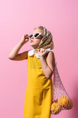 enfant en foulard ajustant les lunettes de soleil tout en tenant un sac à ficelle réutilisable avec des oranges sur rose