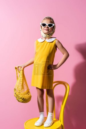 Photo for Happy girl in headscarf and sunglasses holding reusable string bag with bananas while standing with hand on hip on pink - Royalty Free Image