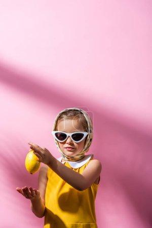 stylish girl in headscarf and sunglasses holding whole lemon on pink