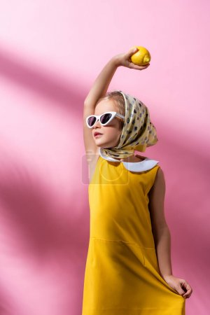 fille élégante en foulard et lunettes de soleil tenant citron au-dessus de la tête sur rose