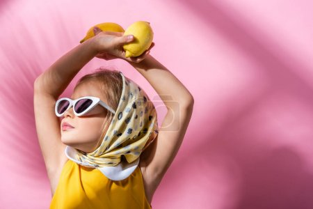 stylish girl in headscarf and sunglasses holding lemons above head on pink