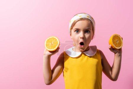 Schockiertes Mädchen mit Kopftuch hält orangefarbene Hälften auf rosa