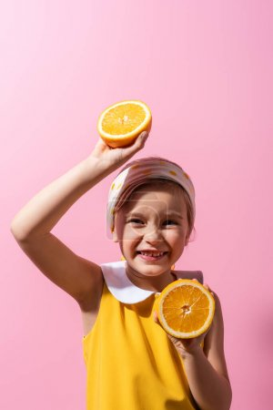 Photo for Smiling girl in headscarf holding orange halves on pink - Royalty Free Image