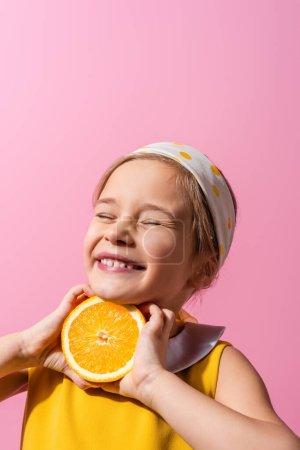 smiling girl with closed eyes holding orange half isolated on pink