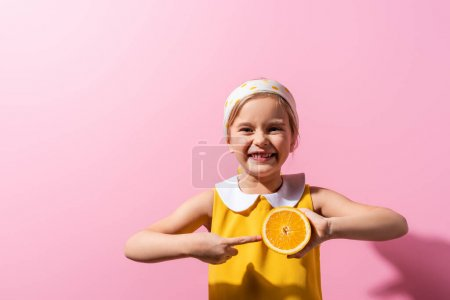 Photo for Positive girl pointing with finger at orange half on pink - Royalty Free Image