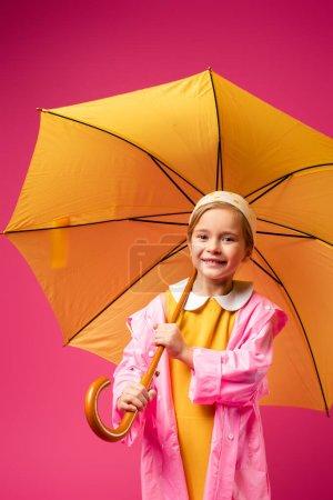 Photo pour Heureux fille en imperméable debout sous parapluie isolé sur cramoisi - image libre de droit