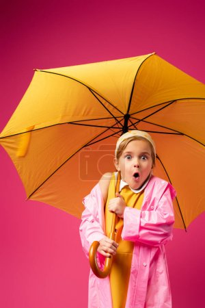 Photo for Shocked girl in raincoat standing under umbrella isolated on crimson - Royalty Free Image