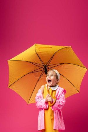 fille étonnée en imperméable debout sous le parapluie sur cramoisi