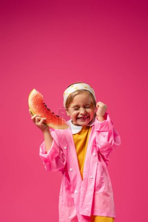 excited girl in raincoat holding watermelon on crimson