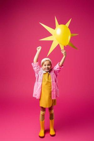 Photo pour Pleine longueur de fille heureuse en imperméable et bottes en caoutchouc tenant soleil décoratif avec ballon sur cramoisi - image libre de droit