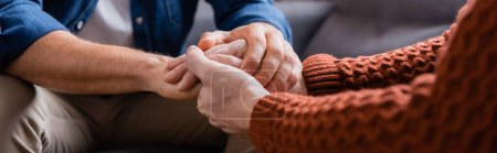 Photo for Cropped view of mature father and young son holding hands at home, blurred foreground, banner - Royalty Free Image