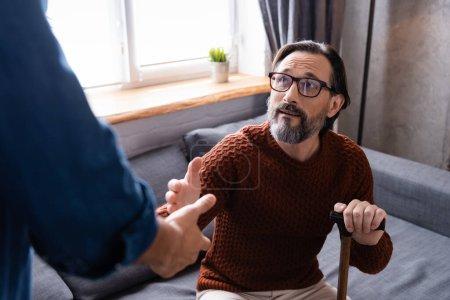 hombre barbudo con la mano extendida cerca de hijo en primer plano borrosa