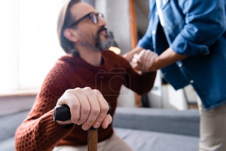Photo for Selective focus of man with walking stick holding hands with son, blurred background - Royalty Free Image