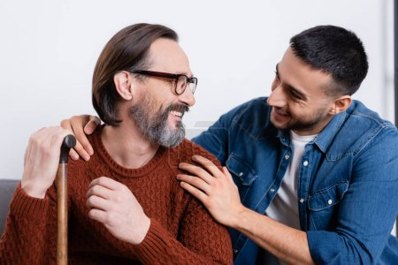 Photo for Smiling hispanic man hugging shoulders of happy father at home - Royalty Free Image