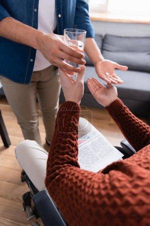 Photo pour Vue partielle de l'homme donnant de l'eau et des pilules au père handicapé, avant-plan flou - image libre de droit