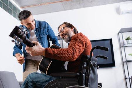 Photo pour Faible angle de vue de l'homme handicapé joyeux jouer de la guitare près excité fils hispanique - image libre de droit