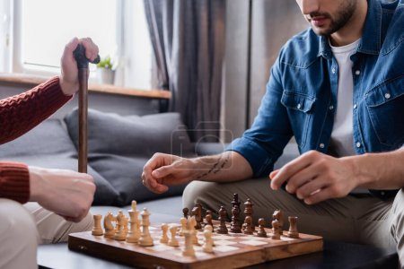 cropped view of young man playing chess with father at home