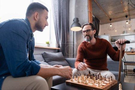 Photo pour Souriant père regardant son fils hispanique tout en jouant aux échecs dans la cuisine - image libre de droit