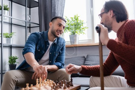 cheerful hispanic man looking at father while playing chess in living room